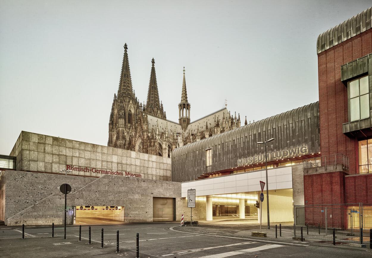 """Vier Kulturen auf einen Blick (v.l.n.r.): Das Römisch-Germanische Museum (1974 erbaut), die römisch-katholische Kirche """"Kölner Dom"""" (Baubeginn 1248), sowie das Museum Ludwig mit der Philharmonie (1986)."""
